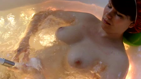 nu : Young woman in a jacuzzi massage the body Vídeos