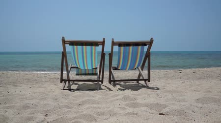 стулья : Two lounge chairs on a beach Стоковые видеозаписи