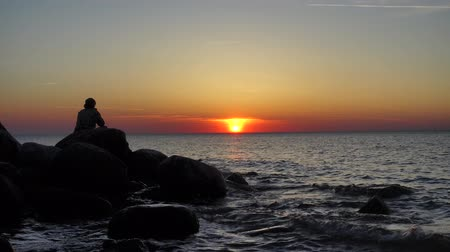 мысль : Man sitting on the stones at the seashore and watching beautiful sunset