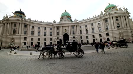 hofburg : VIENNA - APRIL, 24: Tourists ride in a fiakre in old city centre on April 24, 2016 in Vienna
