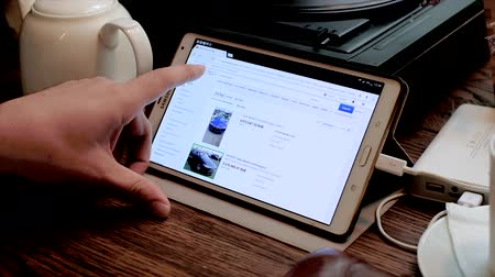 ebay : Moscow, Russia - September 10, 2016: Male hand searching for used tesla car on ebay site using tablet pc in cafe