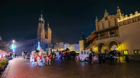marys : Krakow, Poland - December 21, 2016: People visit Christmas market at main square in old city. Timelapse