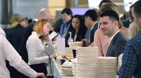 общественное питание : Moscow, Russia - April 24, 2017: Visitors order lunch in a cafe at coffee break at Synergy Global Forum at Crocus Expo Hall. This is one of the largest business forums with more than 5000 participants Стоковые видеозаписи