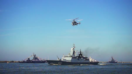 destroyer : Baltijsk, Russia - July 30, 2017: Military naval ship and flying helicopter during a parade to the day of the Russian Navy. Slow motion
