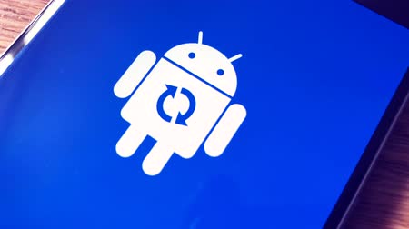 atualizar : Moscow, Russia - April 19, 2018: Android robot logo icon on the smart phone screen during update installation