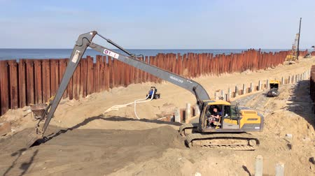 hydraulic : Svetlogorsk, Russia - April 17, 2018: Excavator works on the seashore, strengthening the Baltic Sea coastline, building a new promenade