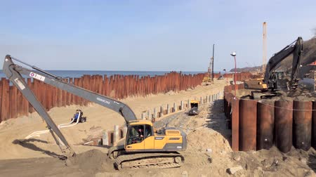 backhoe loader : Svetlogorsk, Russia - April 17, 2018: Excavator works on the seashore, strengthening the Baltic Sea coastline, building a new promenade for the 2018 FIFA World Cup