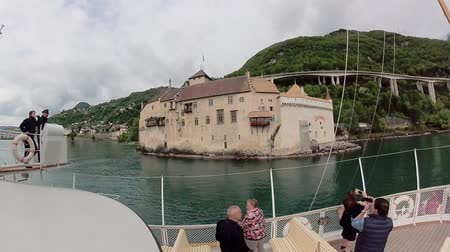 montreux : Montreux, Switzerland - May 2, 2018: Tourist ship sails along the Lake Geneva to the Chillon Castle. Time lapse