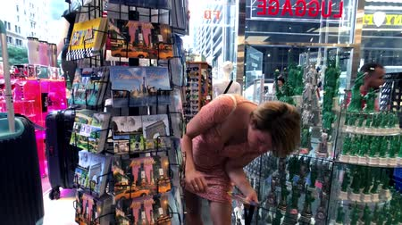 red square : New York, USA - September 6, 2018: Woman choosing post cards in a gift shop on Fifth Avenue
