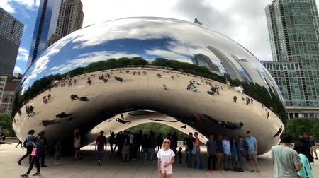 feijões : Chicago, USA - September 6, 2018: Tourists visiting the city landmark sculpture. Cloud Gate is a public sculpture by Indian-born British artist Sir Anish Kapoor