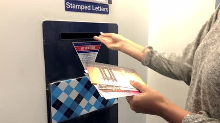 listonosz : New York, USA - September 6, 2018: Woman sending postcards from New York at the United States postal service Wideo