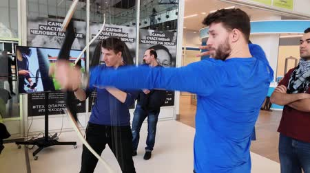 aim : Moscow, Russia - April 24, 2018: Men shooting an archer indoors Stock Footage