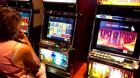štěrbina : Las Vegas, USA - September 10, 2018: Woman playing slot machine in casino