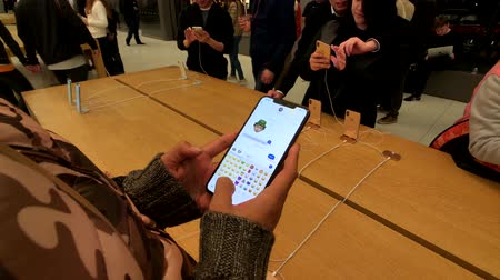 silicon : San Francisco, USA - September 10, 2018: Woman testing new model Iphone XS Max at Apple store, trying to create animoji