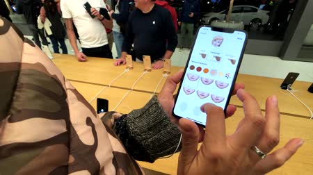 ilustrativo : San Francisco, USA - September 10, 2018: Woman testing new model Iphone XS Max at Apple store, trying to create animoji
