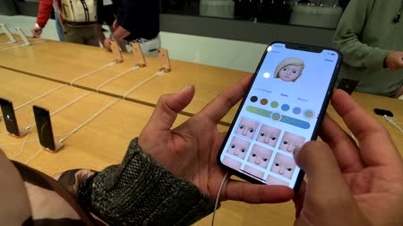 szemléltető : San Francisco, USA - September 10, 2018: Woman testing new model Iphone XS Max at Apple store, trying to create animoji