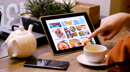 delivery food : Moscow - February 15, 2019: Man looks at pictures of healthy eating on the Internet using tablet pc Stock Footage