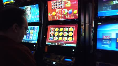 賭け : Las Vegas, USA - September 10, 2018: Man playing slot machine in casino