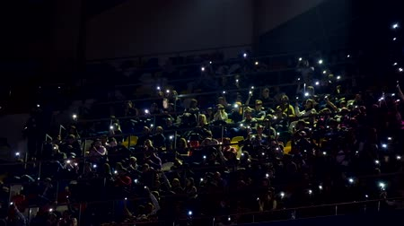 Moscow, Russia - March 13, 2019: Concert fans turned on flashlights on smartphones