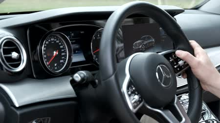 Berlin, Germany - April 16, 2019: Man uses touch controls on the steering wheel Wideo