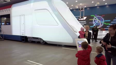 посетитель : Moscow - April 16, 2019: Exhibition visitor choosing the design of future trains on a tablet with a touch screen Стоковые видеозаписи