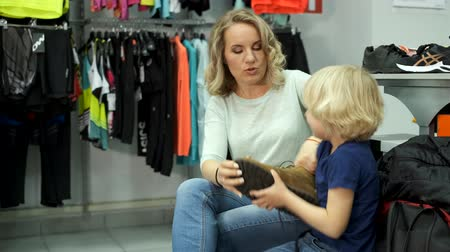 comprador : Pyatigorsk, Russia - April 19, 2019: Mother and son try on sports shoes in a sports store
