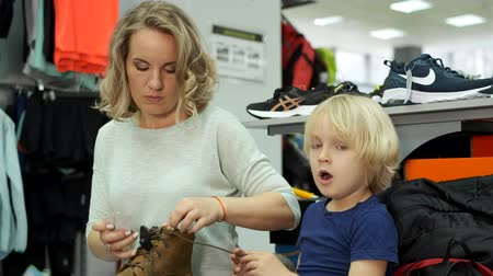 buyer : Pyatigorsk, Russia - April 19, 2019: Mother and son try on sports shoes in a sports store