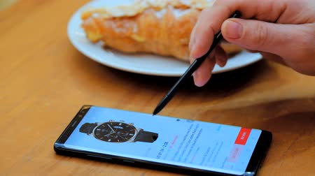 ebay : Frankfurt, Germany - February 15, 2019: Man chooses a watch as a gift on a smartphone screen in an online store sits in a cafe