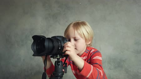 redőnyök : Pyatigorsk, Russia - April 19, 2019: Boy playing with digital camera in studio