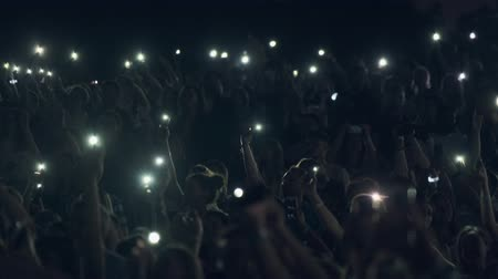 авиашоу : Moscow - June 22, 2019: People attend open-air concert at International Jazz Festival Usadba Jazz in Kolomenskoe Park. They are using flashlights in their smartphones to support the artist on the stage Стоковые видеозаписи