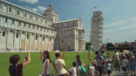 toszkána : Pisa, Italy - August 5, 2019: Tourists visiting the famous landmark leaning tower in the daytime