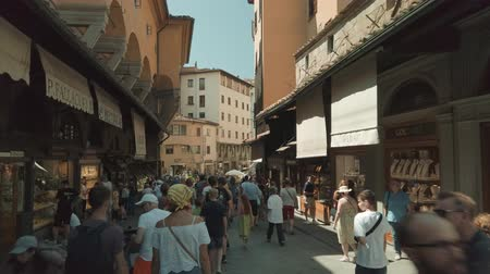 toszkána : Florence, Italy - August 1, 2019: Tourists walking on famous Firenze landmark Ponte Vecchio bridge