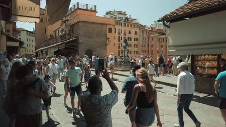 firenze : Florence, Italy - August 1, 2019: Tourists walking on famous Firenze landmark Ponte Vecchio bridge