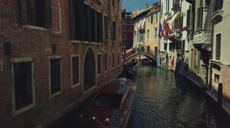 estreito : Venice, Italy - August 1, 2019: Tourists travel by gondola through the canals of Venezia watching landmarks