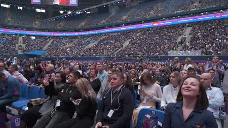 kongres : Saint Petersburg, Russia - October 4, 2019: Business conference attendees sit and cheering to lecturer at large satdium