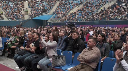 congress : Saint Petersburg, Russia - October 4, 2019: Business conference attendees sit and cheering to lecturer at large satdium