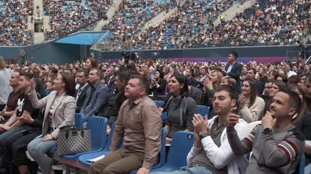 フォーラム : Saint Petersburg, Russia - October 4, 2019: Business conference attendees sit and cheering to lecturer at large satdium