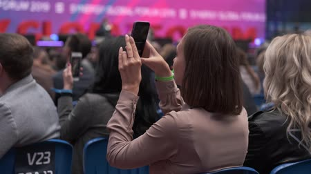 convenção : Saint Petersburg, Russia - October 4, 2019: Woman taking picture of the presentation at the conference hall using smartphone