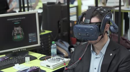 посетитель : Skolkovo, Russia - October 21, 2019: Exhibition visitor tests virtual reality helmet for computer game