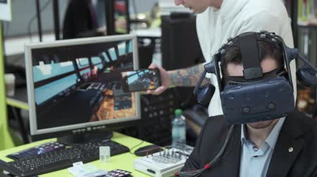 экспозиция : Skolkovo, Russia - October 21, 2019: Exhibition visitor tests virtual reality helmet for computer game