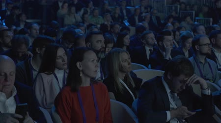 listener : Skolkovo, Russia - October 21, 2019: Visitors to a business forum watch presentation on screen in dark hall