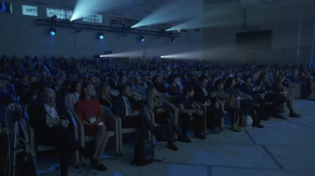listens : Skolkovo, Russia - October 21, 2019: Visitors to a business forum watch presentation on screen in dark hall