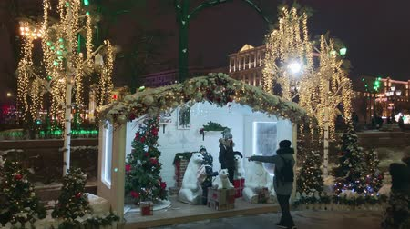 azevinho : Moscow, Russia - December 24, 2019: People walk the streets decorated with illumination for Christmas at evening