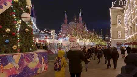 Moscow, Russia - December 24, 2019: People walk the streets decorated with illumination for Christmas at evening