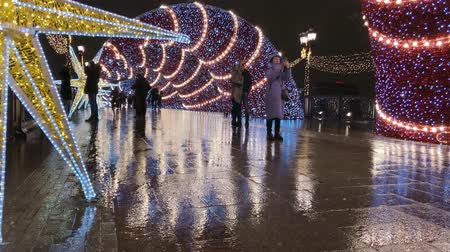 падуб : Moscow, Russia - December 24, 2019: People walk the streets decorated with illumination for Christmas at evening