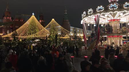 Moscow, Russia - December 24, 2019: People ride a merry-go-round at the Christmas market Wideo