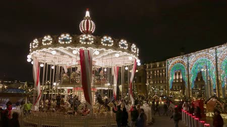 падуб : Moscow, Russia - December 24, 2019: People ride a merry-go-round at the Christmas market Стоковые видеозаписи