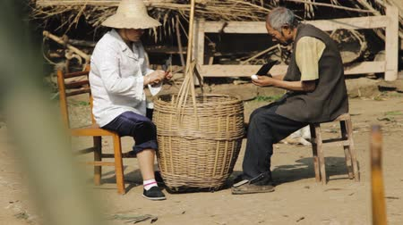 Elderly male and female preparing a root vegetable around a big basket