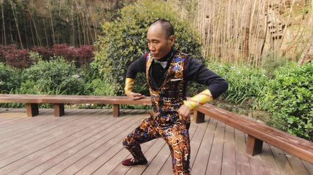 Man performs snake dance on a wooden platform in a park in China