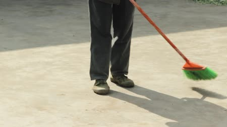 An elderly asian man sweeping the streets with a broom Dostupné videozáznamy